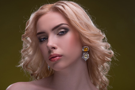 fingering: Half-length portrait of beautiful sexy blonde with evening make up wearing great diamond earrings fingering and bracelet putting her hands on her shoulders looking at us seductively isolated on dark background