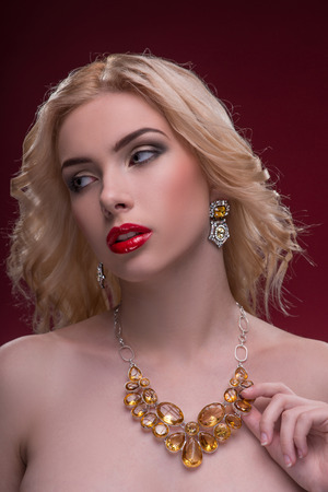 Half-length portrait of beautiful sexy blonde with red tempting lips and perfect skin wearing great jewelry showing us her necklace isolated on dark background