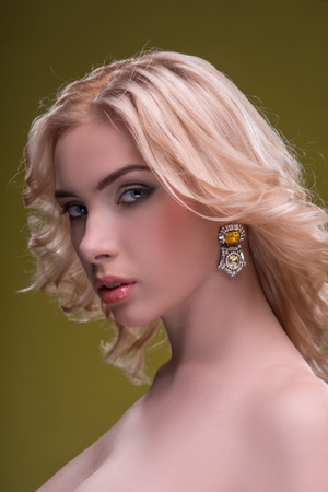 fingering: Half-length portrait of beautiful sexy blonde with evening make up wearing great diamond earrings fingering and bracelet standing aside looking at us seductively isolated on dark background