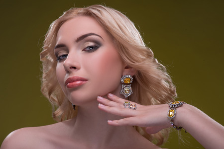 fingering: Half-length portrait of beautiful sexy blonde with evening make up showing her great diamond earrings fingering and bracelet looking at us seductively isolated on dark background Stock Photo