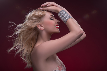 Half-length portrait of beautiful sexy blonde with red tempting lips and perfect skin wearing precious bracelet standing aside touching her hair isolated on dark background Stock Photo
