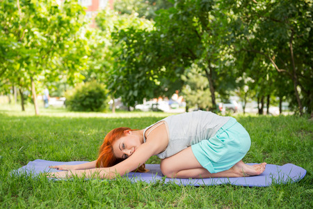 mat like: Pretty young red-haired woman wearing white T-shirt and mental shorts doing yoga lying like a ball on the blue mat in the park