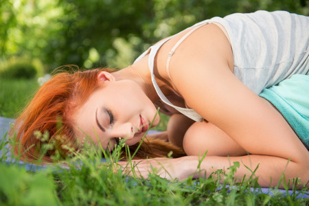 Pretty young red-haired woman wearing white T-shirt and mental shorts doing yoga lying like a ball on the blue mat in the park