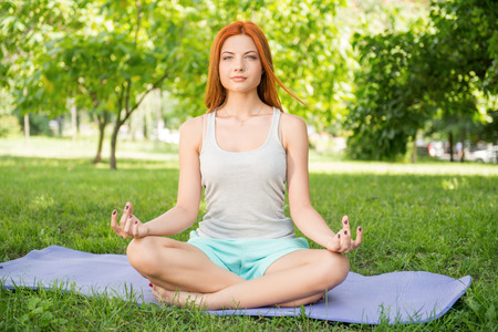 Pretty young red-haired woman wearing white T-shirt and mental shorts sitting on the blue mat doing yoga in the park lotus pose photo