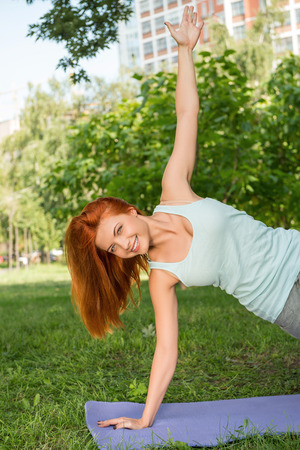 Pretty young red-haired woman wearing white T-shirt and grey pants doing yoga pressing out of the ground on blue mat in the park  photo