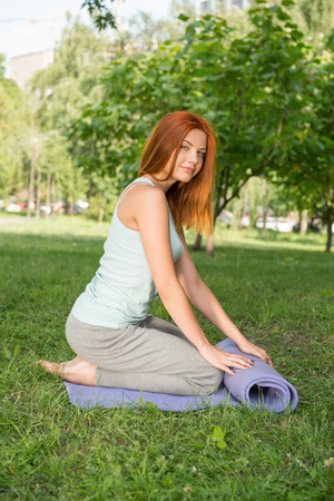 Pretty young red-haired woman wearing white T-shirt and grey pants doing yoga twisting her blue mat in the park  photo