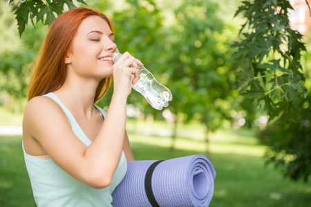 Selective focus on pretty young red-haired woman wearing white T-shirt standing aside drinking water and smiling satisfied with her life. Park on background photo