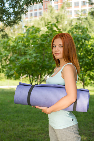 Pretty young smiling red-haired woman wearing white T-shirt and grey pants standing aside in the park with the blue mat and bottle of water  photo