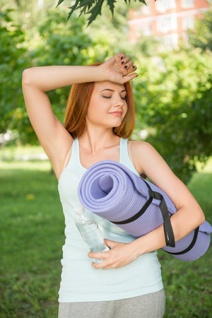 Pretty young red-haired woman wearing white T-shirt and grey pants standing in the park with the blue mat and bottle of water wiping her forehead photo