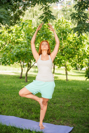 Pretty young red-haired woman wearing white T-shirt and mental shorts doing yoga standing in the pose lotus on the blue mat in the park  photo