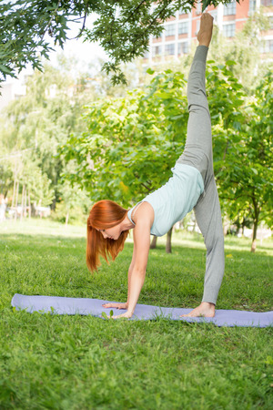 yoga pants: Pretty young red-haired woman wearing white T-shirt and grey pants doing yoga standing on the one hand on blue mat in the park