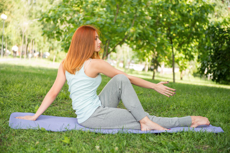 yoga pants: Pretty young red-haired woman wearing white T-shirt and grey pants doing yoga stretching crossing her legs on blue mat in the park  Stock Photo