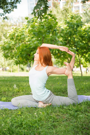 yoga pants: Pretty young red-haired woman wearing white T-shirt and grey pants doing yoga stretching her legs and hands sitting on blue mat in the park