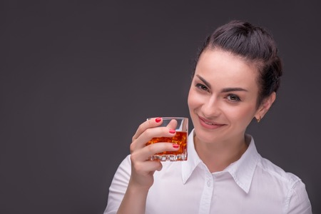 proposing a toast: Half-length portrait of dark-haired smiling beautiful woman wearing white blouse standing aside holding a glass of whisky proposing a toast for us. Isolated on dark background Stock Photo