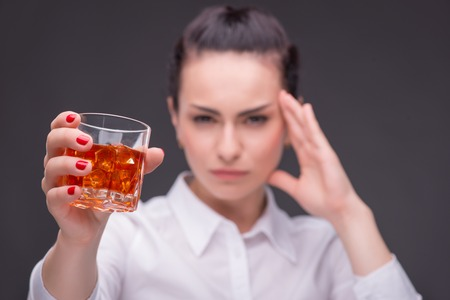 Selective focus on the glass of whisky in the hands of dark-haired tired beautiful woman wearing white blouse thinking hard about something on background photo