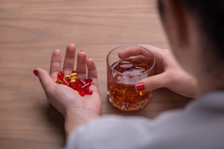 Selective focus on the glass of whisky in one hand and a pile of colorful pills in another of dark-haired upset woman wearing white blouse sitting at the table thinking about the most important decision in her life. Top view photo
