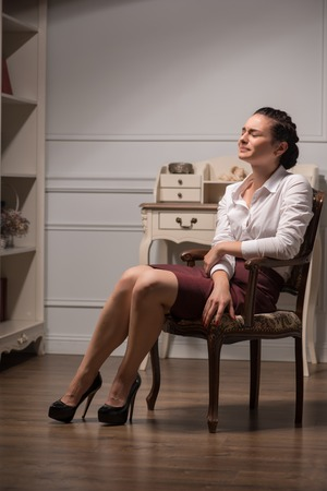 Full-length portrait of beautiful dark-haired young sad woman wearing white blouse and vinous skirt sitting in the chair in the office who is brought to bay photo