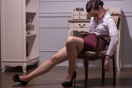 sapless: Full-Length ritratto di bella dai capelli scuri giovane donna sapless che indossa camicia bianca e gonna vinoso dormire sulla sedia nel suo ufficio