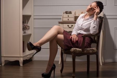 sapless: Ritratto a figura intera di una bella ragazza dai capelli giovane donna senza linfa che indossa camicia bianca e gonna vinoso dormire sulla sedia nel suo ufficio