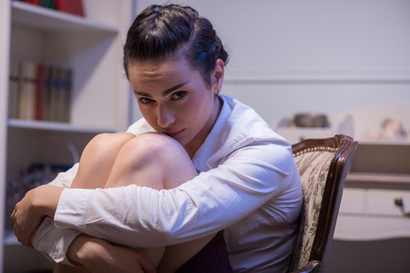 Selective focus on the beautiful dark-haired young poor woman wearing white blouse sitting in the chair flexing her legs and thinking how to solve her problems. Her office on background photo