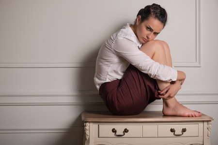 table skirt: Full-length portrait of beautiful dark-haired thoughtful young woman wearing white blouse and vinous skirt sitting on the little table leaning to the wall Stock Photo