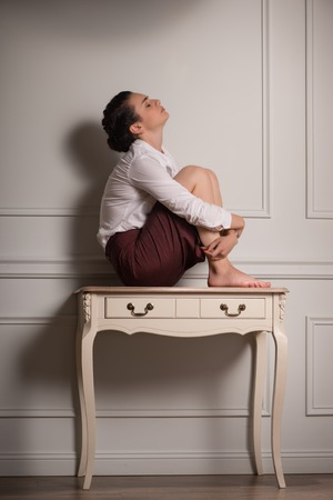 Full-length portrait of beautiful dark-haired fagged young woman wearing white blouse and vinous skirt sitting on the little table leaning to the wall thinking about her husband photo