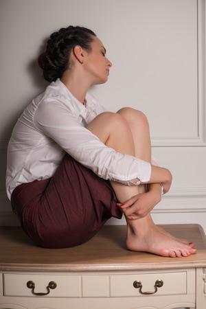 sapless: Full-length ritratto di donna d'affari stanco che indossa camicia bianca e gonna vinoso seduto sul tavolo con gli occhi chiusi appoggiato al muro Archivio Fotografico