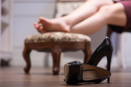 sapless: Selective focus on the black bootees lying on the floor near the chair. A barefooted woman on background