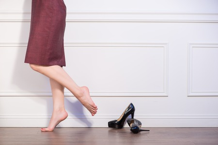 sapless: Half-length portrait of barefooted woman wearing vinous skirt standing at the wall near her black bootees Stock Photo
