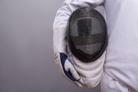 フェンシング マスクを保持している白いフェンシングのコスチュームを着ている少女の半身像。 写真素材
