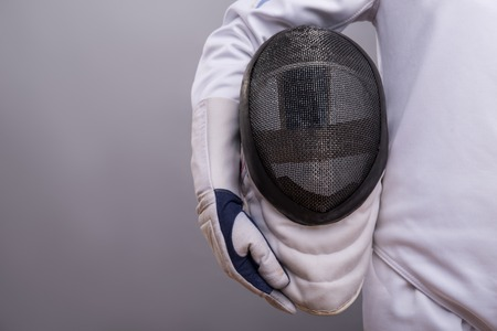 rapier: Half-length portrait of the girl wearing white fencing costume holding the fencing mask.  Stock Photo