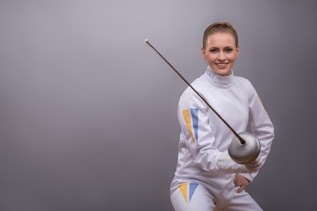 rapier: Half-length portrait of pretty smiling girl wearing white fencing costume holding a rapier in her hand waiting for the adversary.