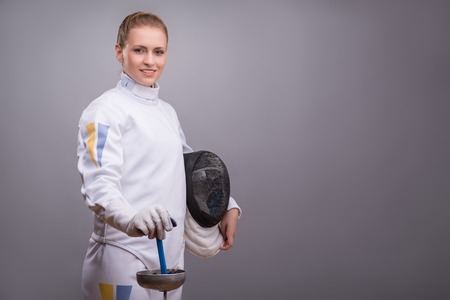 rapier: Half-length portrait of the fair-haired smiling girl wearing white fencing costume standing aside holding the fencing mask in one hand and a rapier in another.