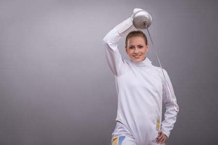 rapier: Half-length portrait of pretty smiling girl wearing fencing costume practicing in fencing with her rapier.