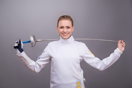 rapier: Half-length portrait of pretty smiling girl wearing fencing costume holding her sword on the shoulders thinking about her victory. Isolated on dark background