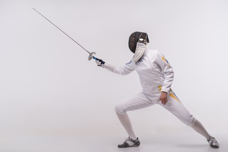 Full-length portrait of woman wearing white fencing costume and black fencing mask practicing with the sword. Isolated on white background Stock fotó