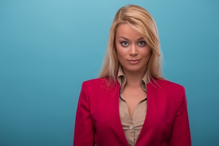 Half-length portrait of very beautiful fair-haired enigmatic TV presenter wearing great red jacket and cream-colored shirt thinking about something. Isolated on blue background photo