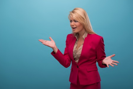 proving: Half-length portrait of very beautiful fair-haired excited TV presenter wearing great red jacket and cream-colored shirt proving something. Isolated on blue background