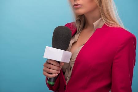 hablar en publico: Retrato de medio cuerpo de rubia presentadora de televisi�n serio llevaba gran chaqueta de color rojo y una camisa de color crema a hablar por el micr�fono. Aislado en el fondo azul Foto de archivo