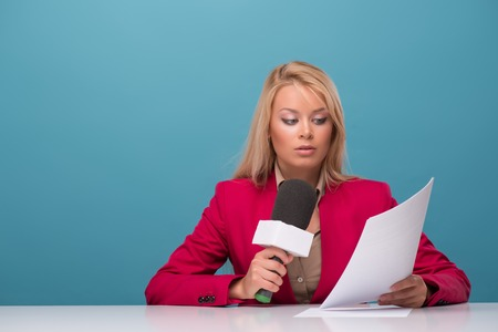 fresh news: Half-length portrait of good-looking fair-haired surprised TV presenter wearing great red jacket and cream-colored shirt sitting at the table reading fresh news. Isolated on blue background