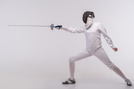 Full-length portrait of woman wearing white fencing costume and black fencing mask standing with the sword practicing in fencing. Isolated on white background