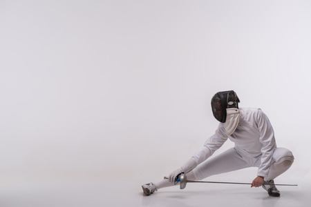Full-length portrait of woman wearing white fencing costume and black fencing mask sitting like ninja looking at us. Isolated on white background