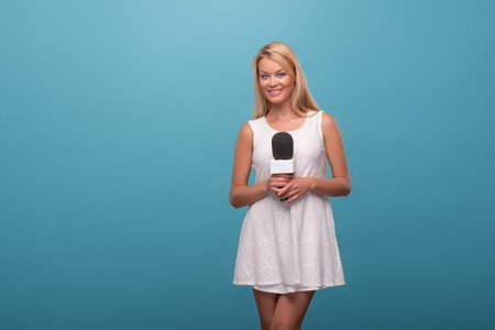 Half-length portrait of lovely fair-haired smiling TV presenter wearing pretty white dress standing holding a microphone. Isolated on blue background photo