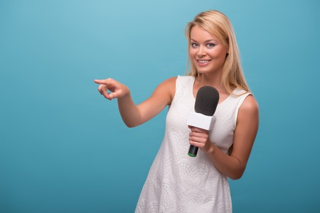 Half-length portrait of lovely fair-haired smiling TV presenter wearing pretty white dress standing holding a microphone pointing at someone. Isolated on blue background photo