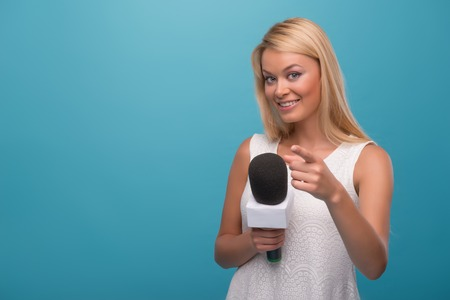 Half-length portrait of lovely smiling fair-haired TV presenter wearing pretty white dress holding a microphone showing that she likes her job. Isolated on blue background