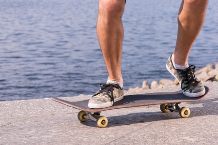 Half-length portrait of the man wearing shorts and trainers riding a skateboard on the quay photo