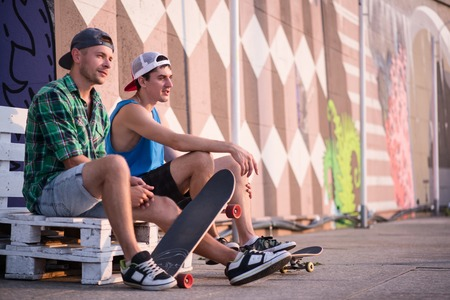 Full-length portrait of two young men sitting aside on the white bench on the street showing each other their skateboards talking about their favorite sport activity photo