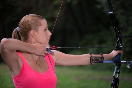Selective focus on the lovely young fair-haired woman standing aside wearing pink T-shirt pulling the bowstring