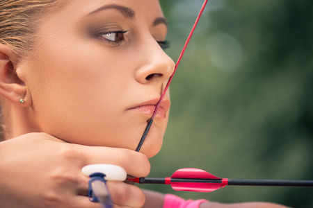 active arrow: Selective focus on the lovely young fair-haired woman pulling the bowstring