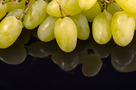 vitreous: A bunch of wonderful big delicious grapes lying on the black vitreous surface